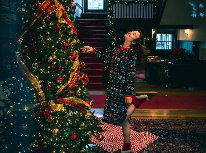 woman happily decorating christmas tree