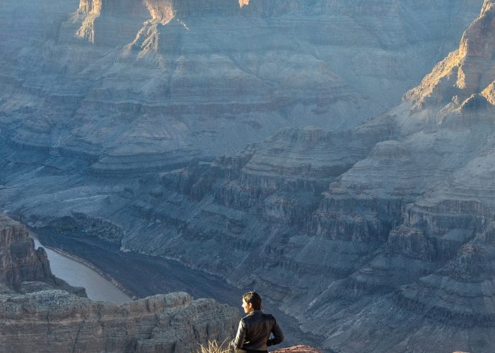 Woman alone staring into the Grand Canyon