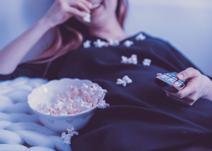 woman in bed watching movie with popcorn