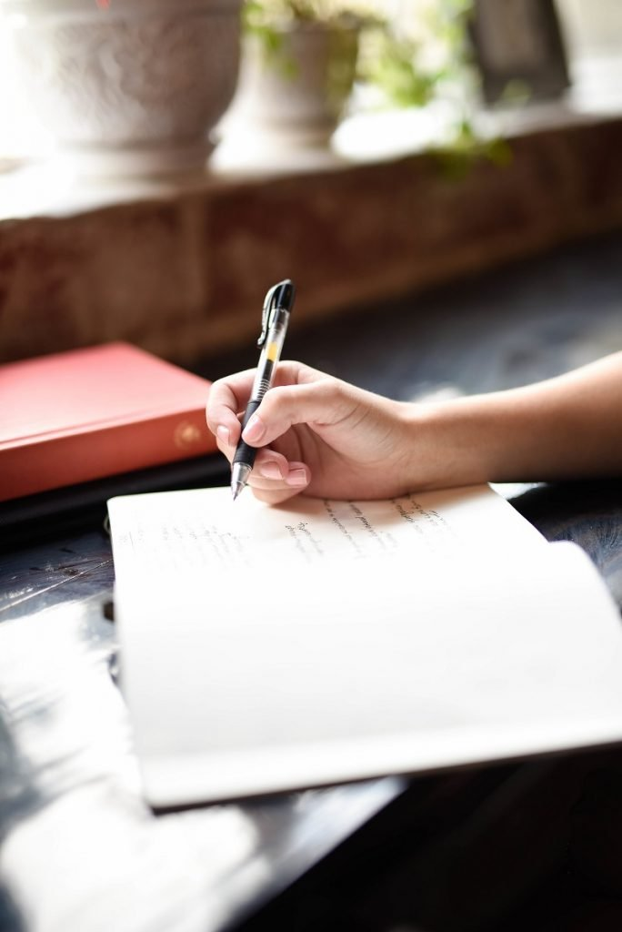 woman's hand writing in a notebook