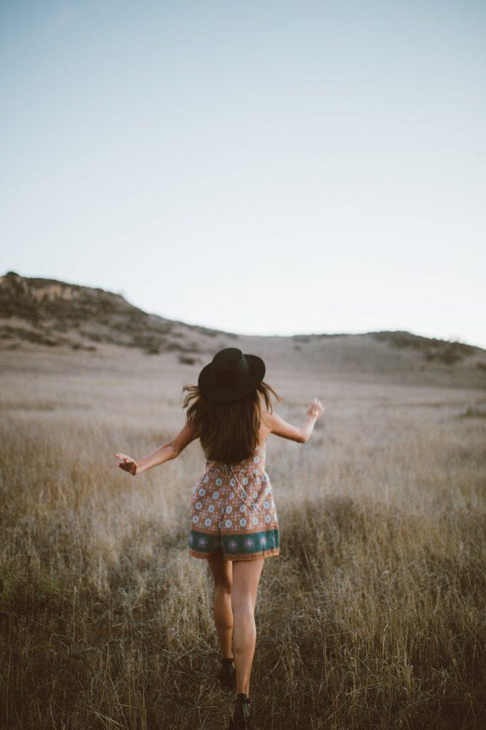 woman walking across field to get up hill
