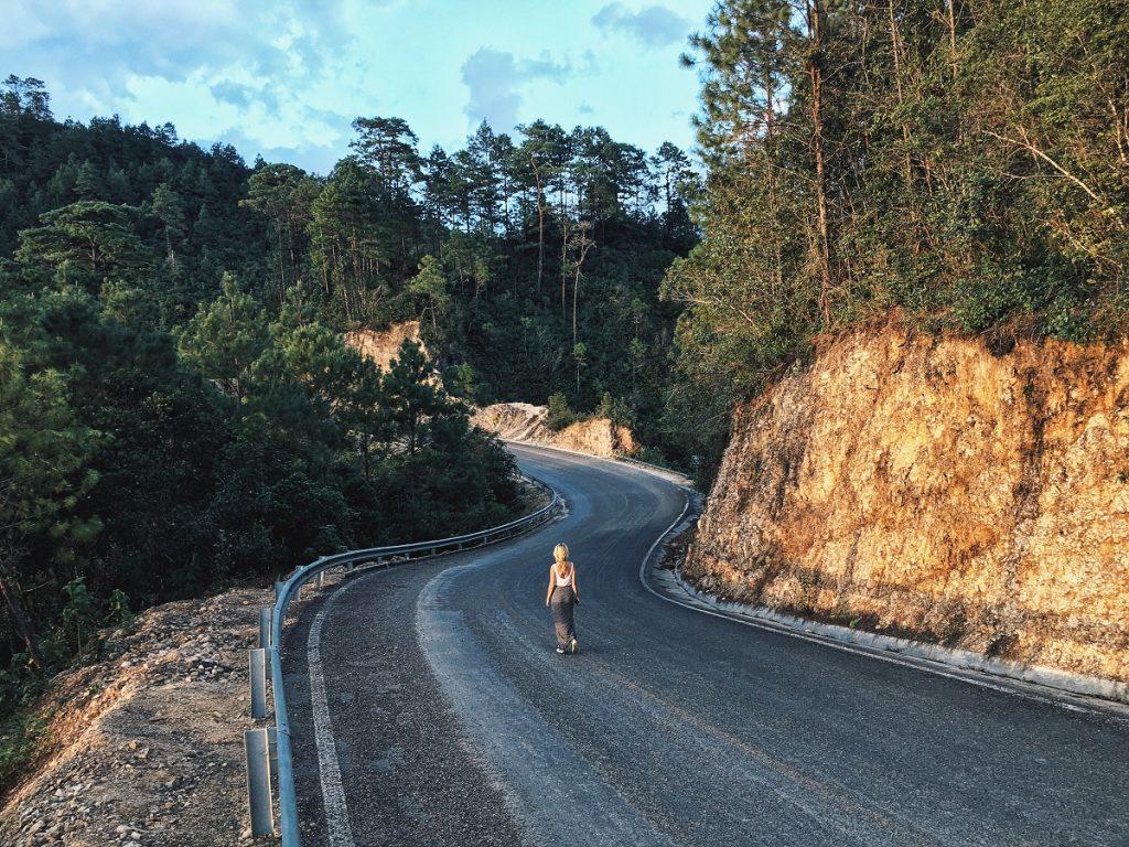 woman walking a winding road alone toward blue sky