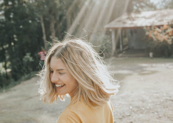 woman smiling with sun shining in her face