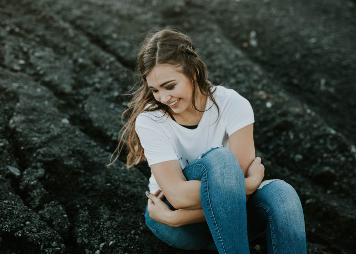 woman hugging knees and smiling