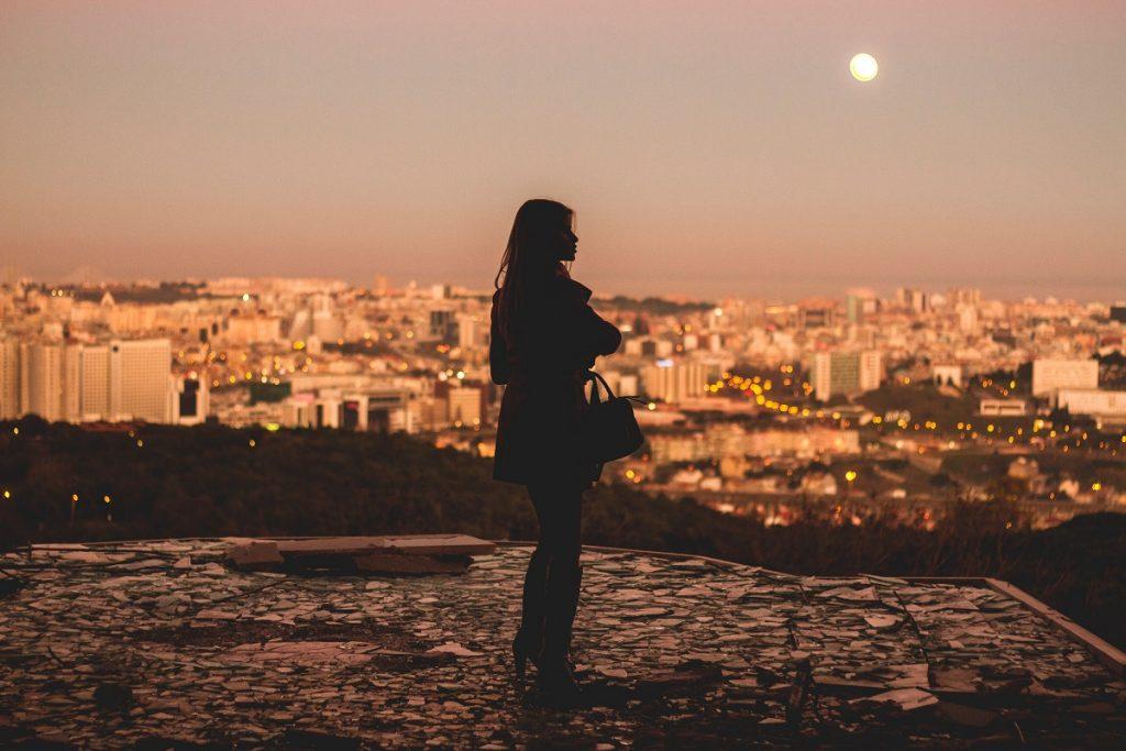 single woman overlooking a big city