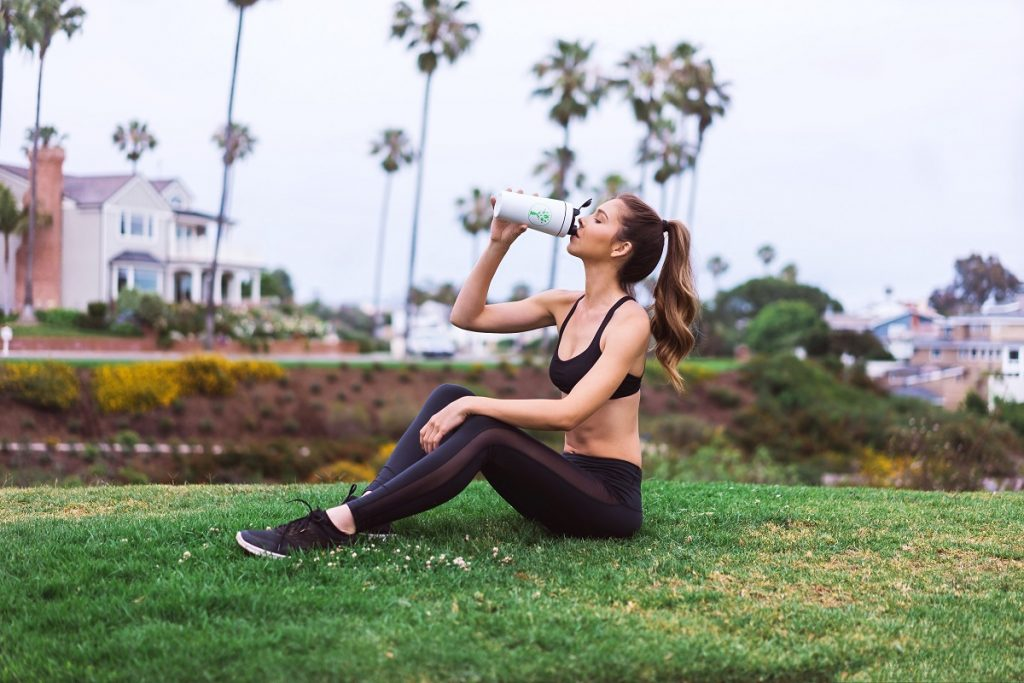 woman in fitness clothes post-workout sitting on the grass drinking water