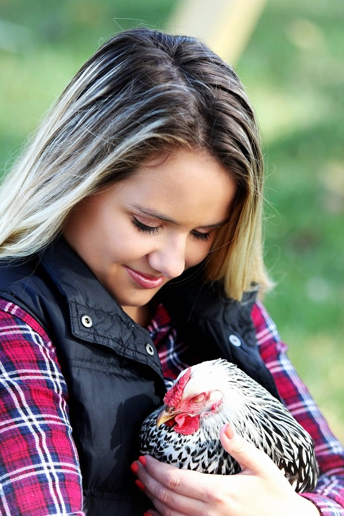 woman holding chicken and smiling at it