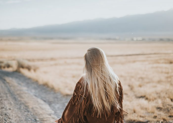 woman walking down deserted country road looking dejected