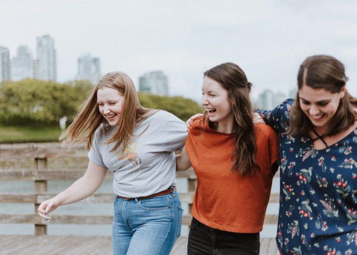 three women walking arm in arm