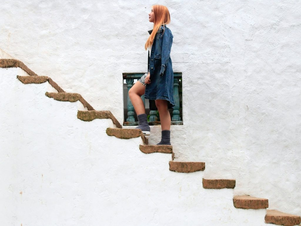 woman looking up while climbing stairs