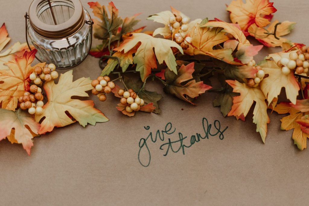 """fall leaves and a candle on a table with the words """"give thanks"""""""