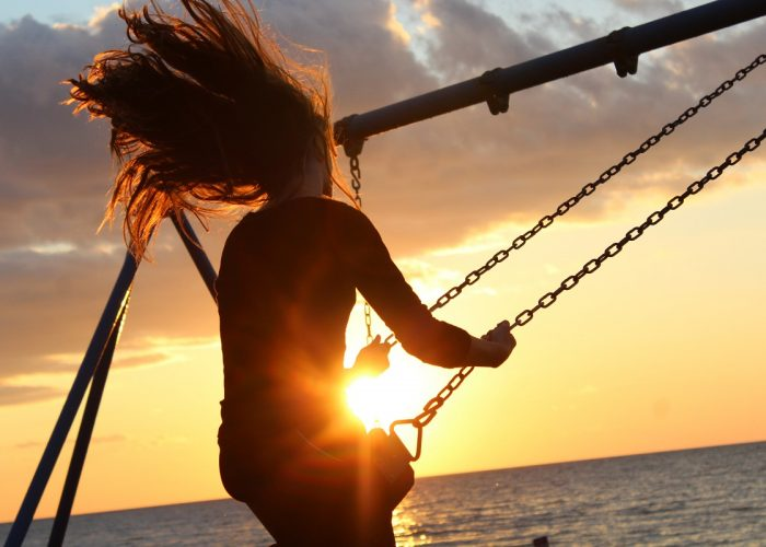 woman-swinging-on-swingset-at-sunset